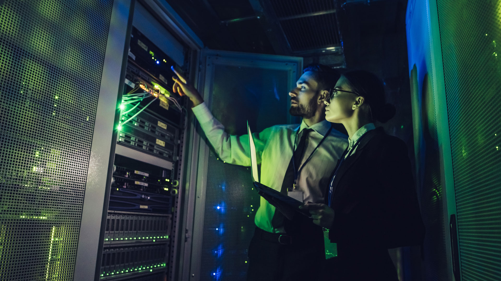 Man and Woman in Data Centre looking at a server rack